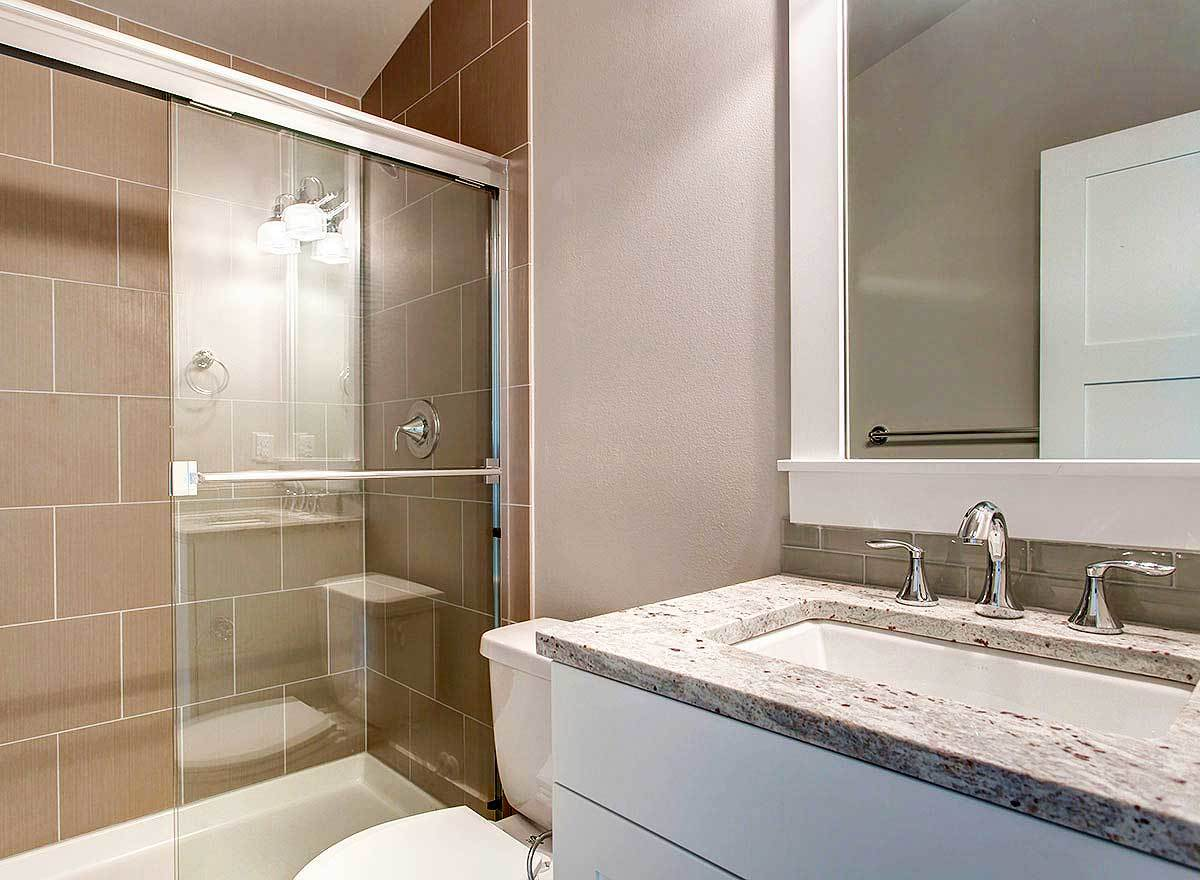 The bathroom has a sleek sink vanity, a toilet, and a tub and shower combo.
