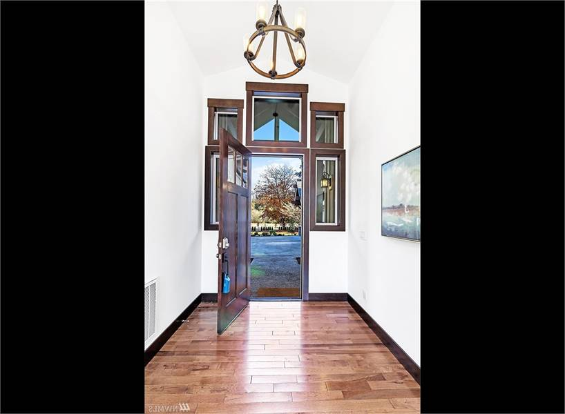 The foyer has a dark wood entry door and a round chandelier that hangs from the vaulted ceiling.