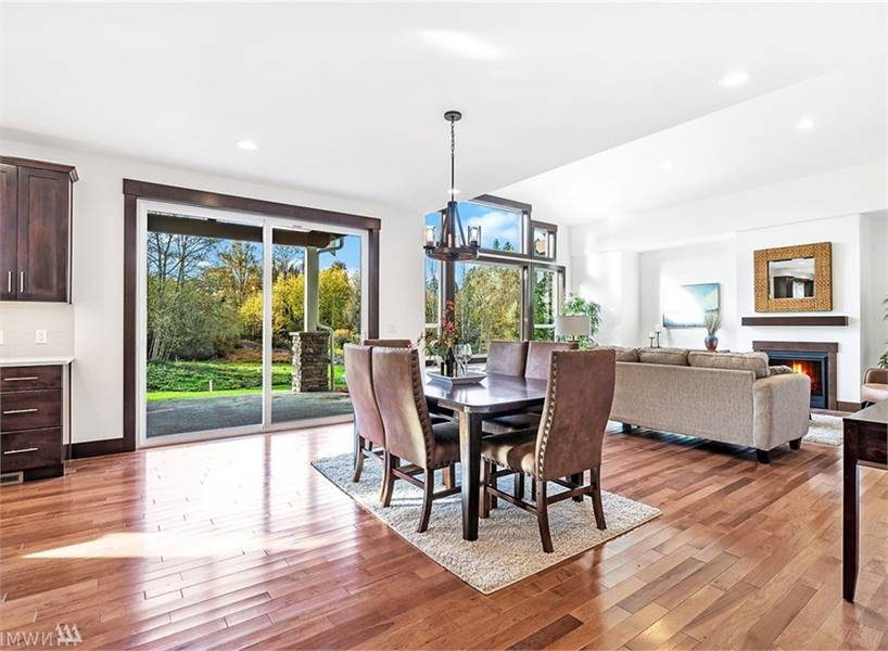 The dining room offers a small chandelier, leather high back chairs, and a wooden dining table sitting on a beige rug.