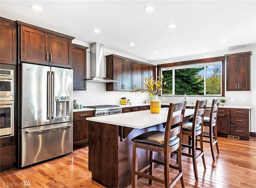 The kitchen is equipped with stainless steel appliances, wooden cabinetry, and a breakfast island.