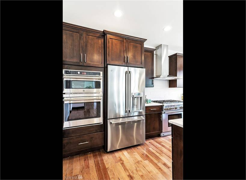 Stainless steel appliances include the double wall oven, two-door fridge, cooking range, and a sleek vent hood.