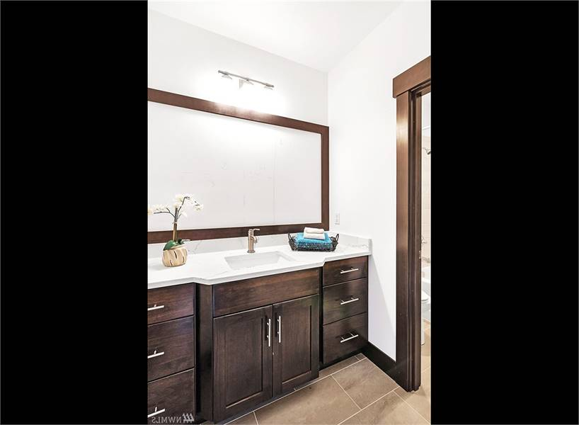 This bathroom features a sink vanity with dark wood cabinets, marble countertop, and a large rectangular mirror.