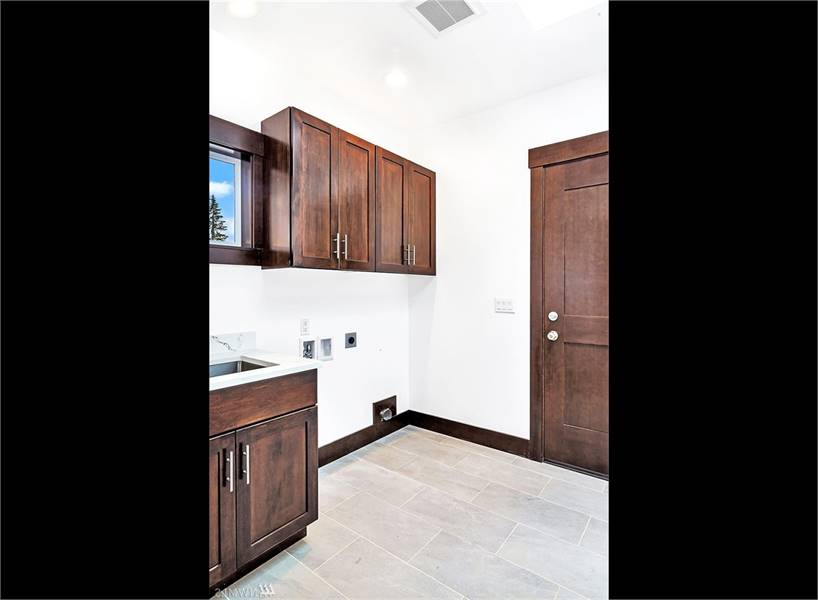 The laundry has tiled flooring, undermount sink, and wooden cabinets that match the rustic door.