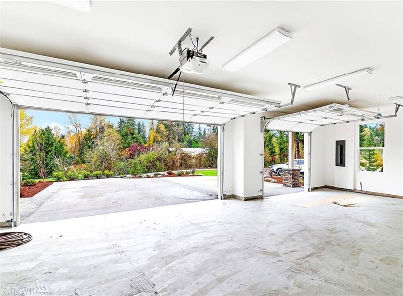 Three-car garage with concrete flooring and metal doors.
