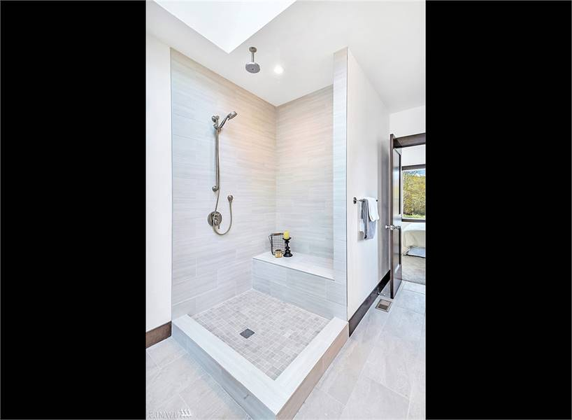 The shower area has two shower heads and a tiled bench that blends in with the walls.