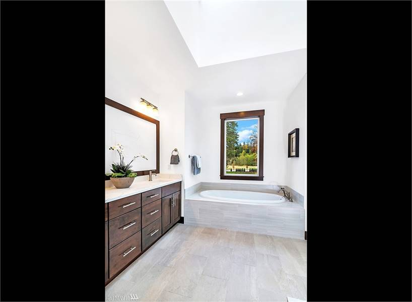 Primary bathroom equipped with dual sink vanity and a drop-in bathtub fixed under the picture window.