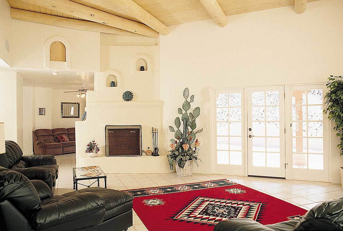 The living room offers a kiva fireplace, black leather armchairs, and a red printed rug that lays on the white tiled flooring.