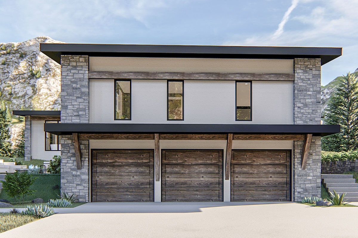 Left side view showing the three-car garage enclosed in rustic wood doors.