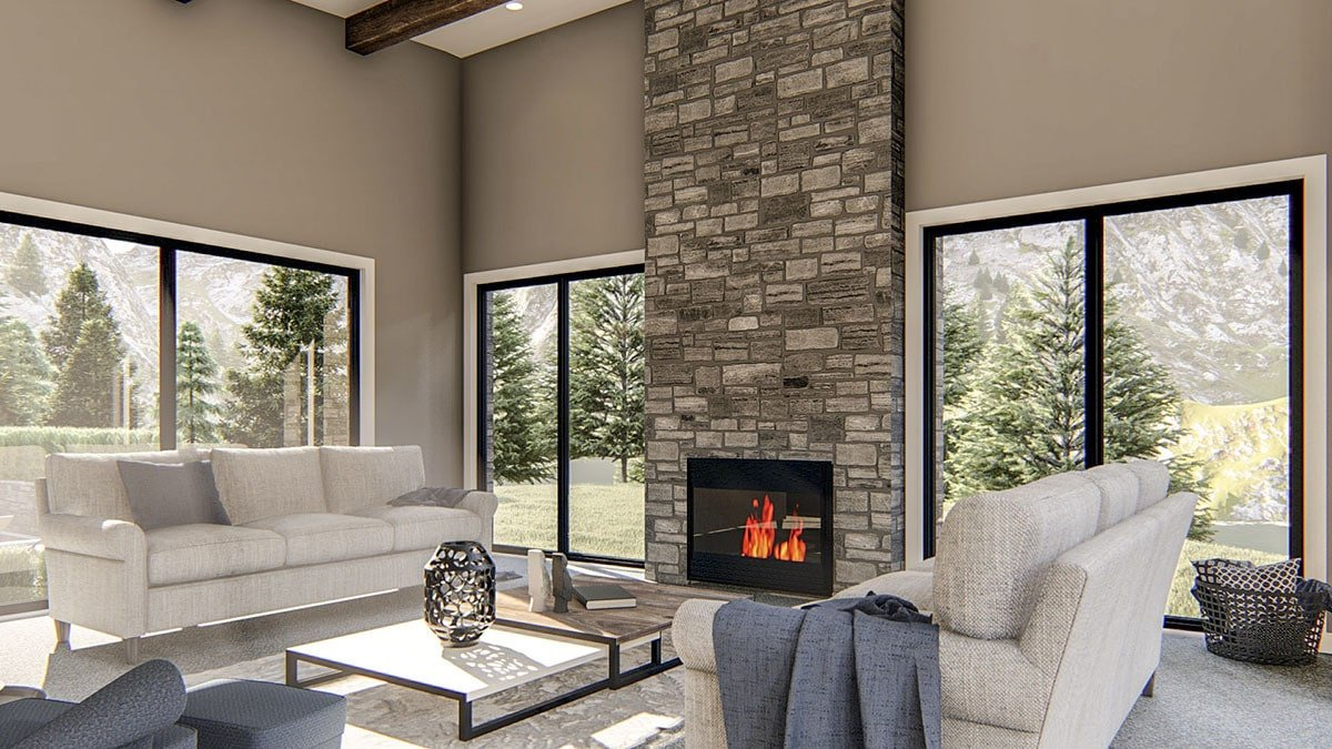 Living room with a stone fireplace, modular coffee table, and gray sectional sofas that blend in with the carpet flooring.