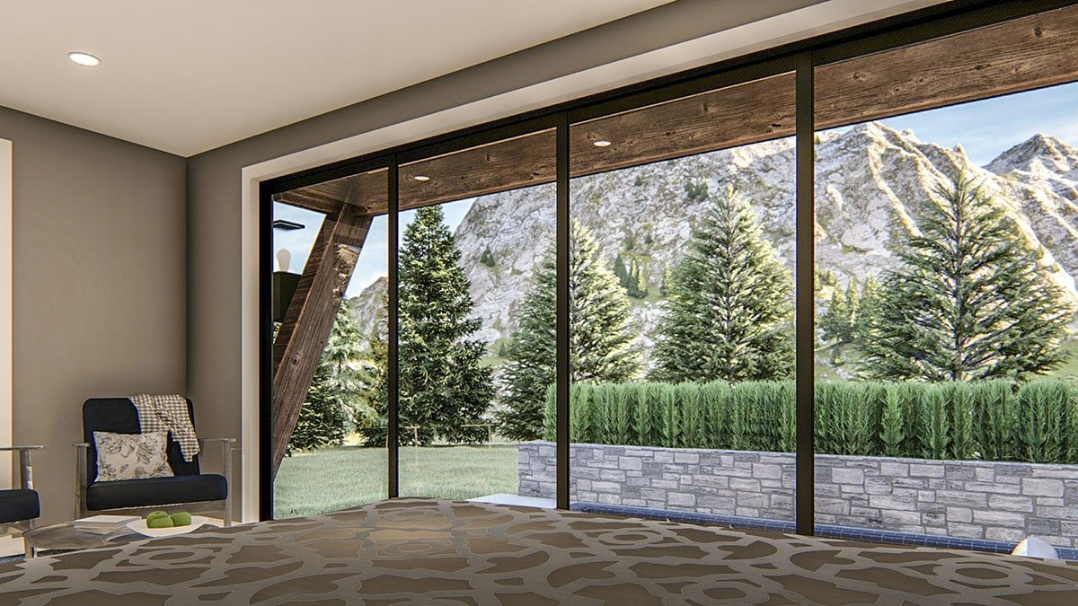 Sitting area in the primary bedroom with black armchairs and a panoramic window that overlooks the stunning mountain.