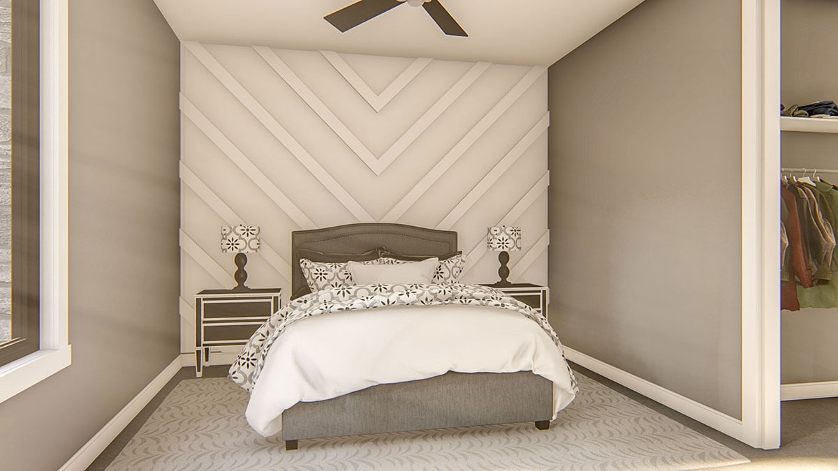 This bedroom has a closet and a gray upholstered bed flanked by matching nightstands.