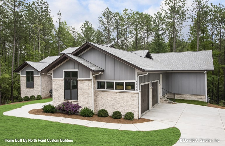 Side exterior view showing the double garage and a curved concrete driveway.