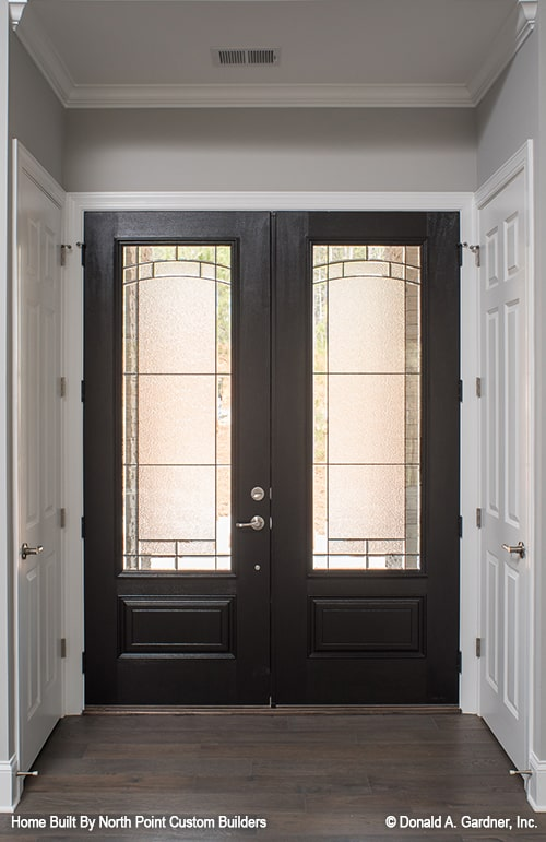 The foyer features a dark wood french door fitted with stained glass panels.