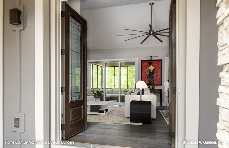 The French entry door opens to the living room with a vaulted ceiling and hardwood flooring.