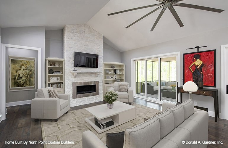 Living room with gray seats, white coffee table, and a modern fireplace with a TV on top.