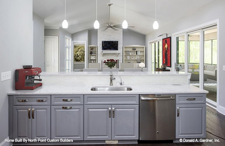 A series of glass dome pendants hang over the two-tier peninsula that's fitted with an undermount sink.