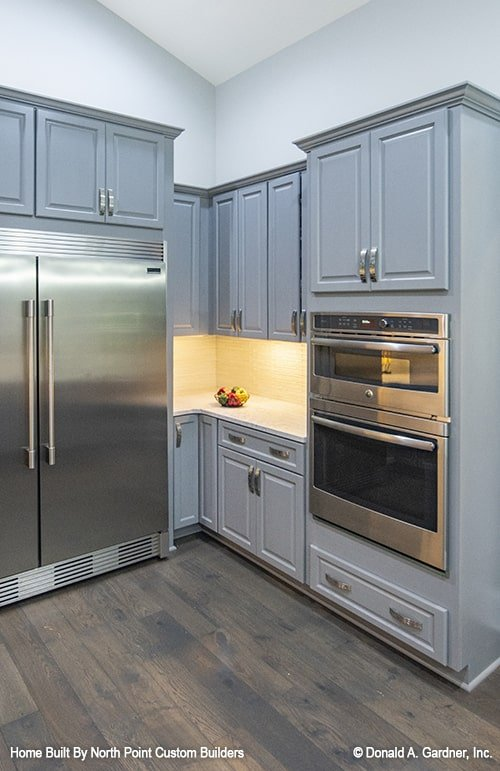The kitchen is equipped with gray cabinets, a two-door fridge, and a double wall oven.