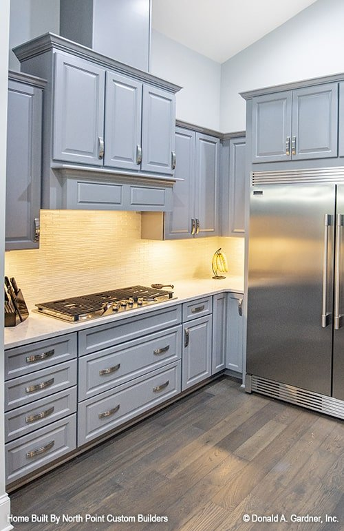 Built-in cooktop and a bespoke vent hood that matches the cabinets complete the kitchen.