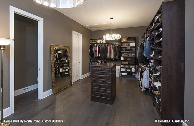 Spacious walk-in closet with dark wood shelves, gilded mirror, a small center island, and round chandeliers.
