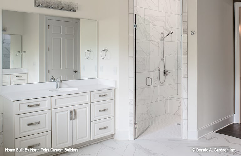 The primary bathroom offers a walk-in shower and a white sink vanity paired with a frameless mirror.