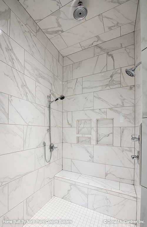 The walk-in shower has a tiled bench, marble walls, chrome fixtures, and inset shelves.