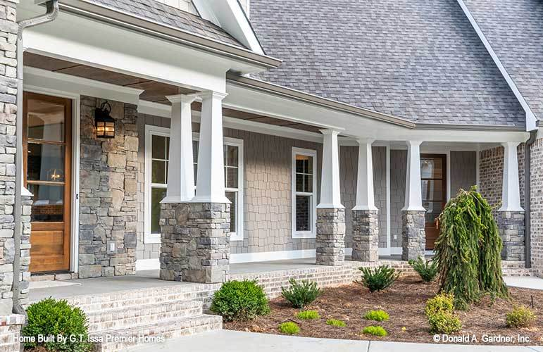 Home's entry showing the wooden front door and a wide porch lined with tapered columns.