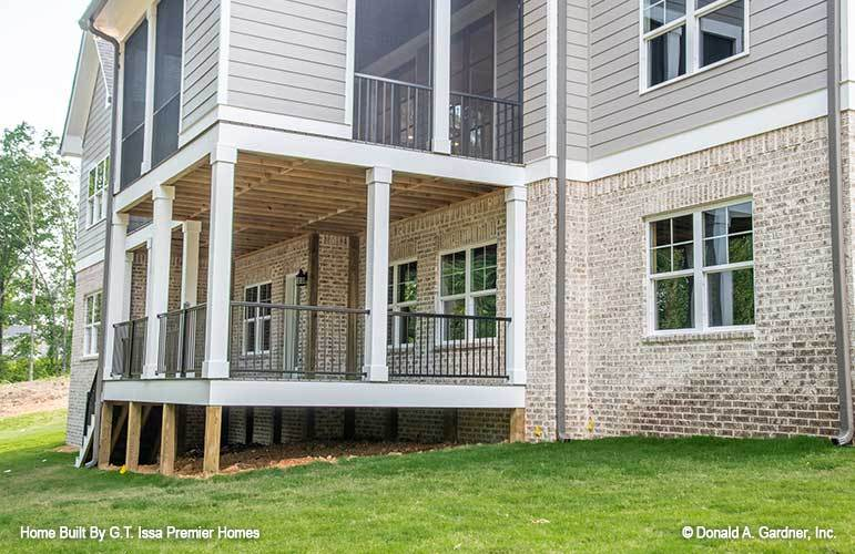 Rear exterior view with screened porch and a covered deck enclosed in wrought iron railings and white columns.