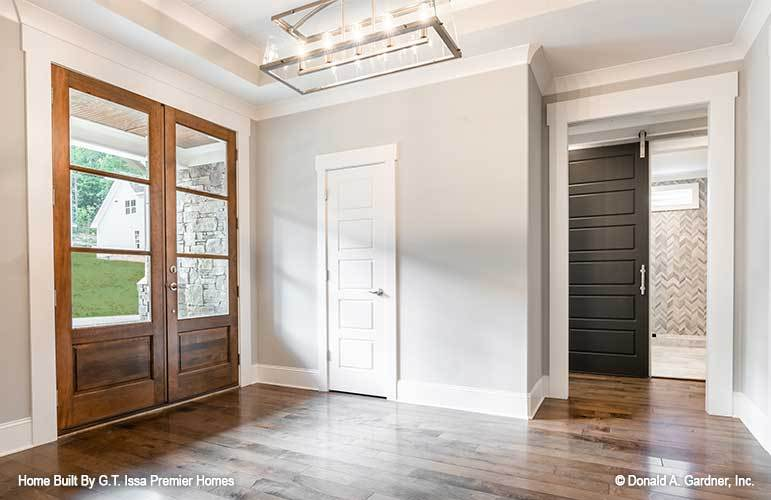 The foyer has a wooden french entry door and a large chandelier that hangs from the tray ceiling.