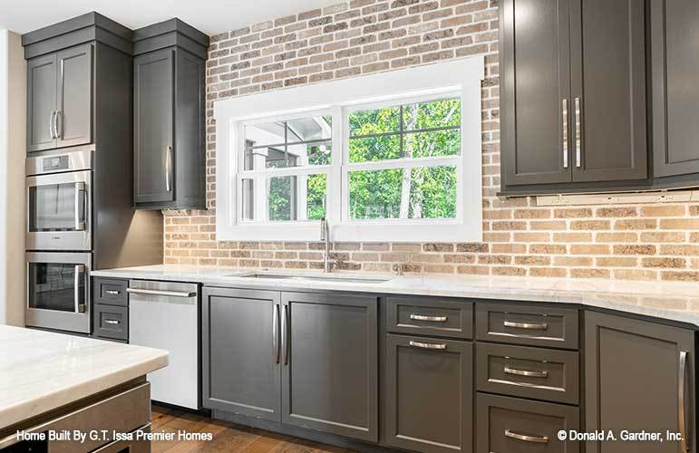 White marble countertops, stainless steel appliances, and dark wood cabinetry against the brick backsplash fill the kitchen.