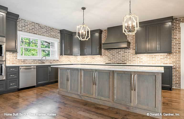 A pair of candle pendant lights hanging above the wooden center island illuminate the kitchen.