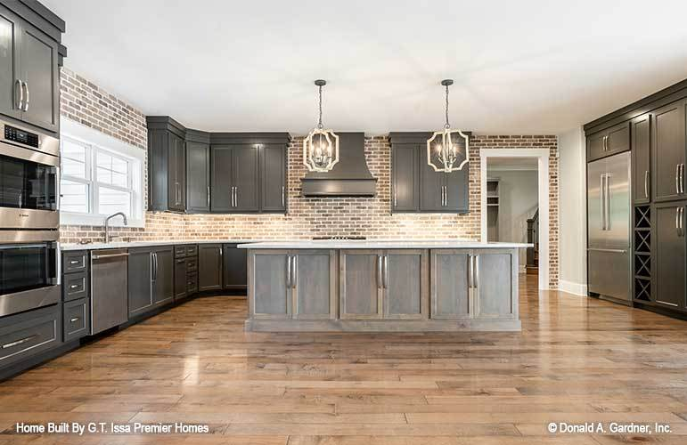 A farther view of the kitchen shows the two-door fridge, crisscross wine racks, and an open doorway that leads to the mudroom.
