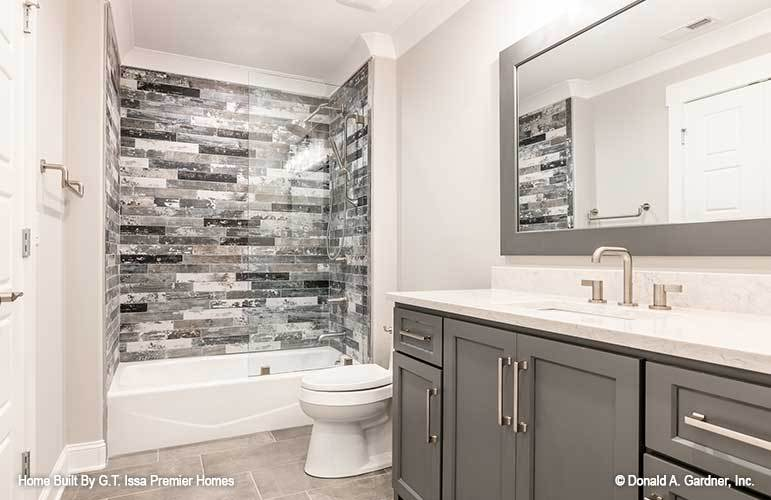 This bathroom offers a marble top vanity, a toilet, and a tub and shower combo accentuated with black linear mosaic tiles.