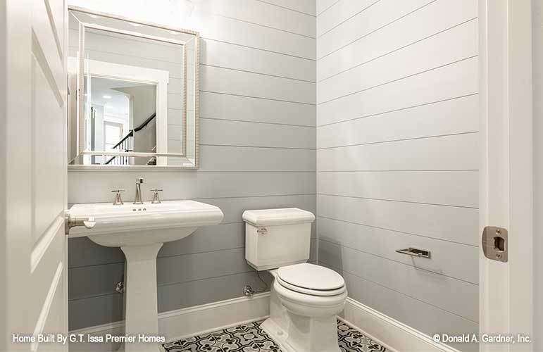Another bathroom with a toilet, a sink pedestal, and a chrome framed mirror fixed against the gray shiplap wall.
