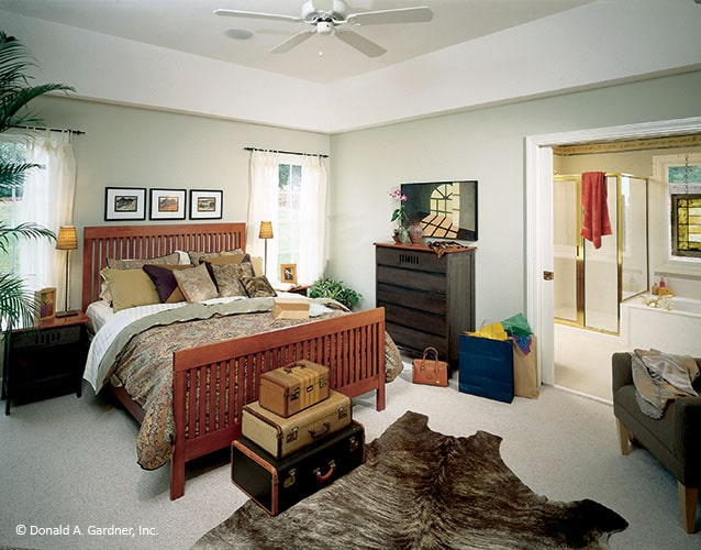 Primary bedroom with gray walls, wooden furnishings, cowhide rug, and a full ensuite.