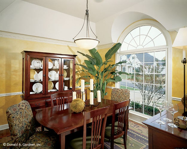 The dining room has a coved ceiling, yellow walls, and a massive arched window overlooking the outdoor scenery.