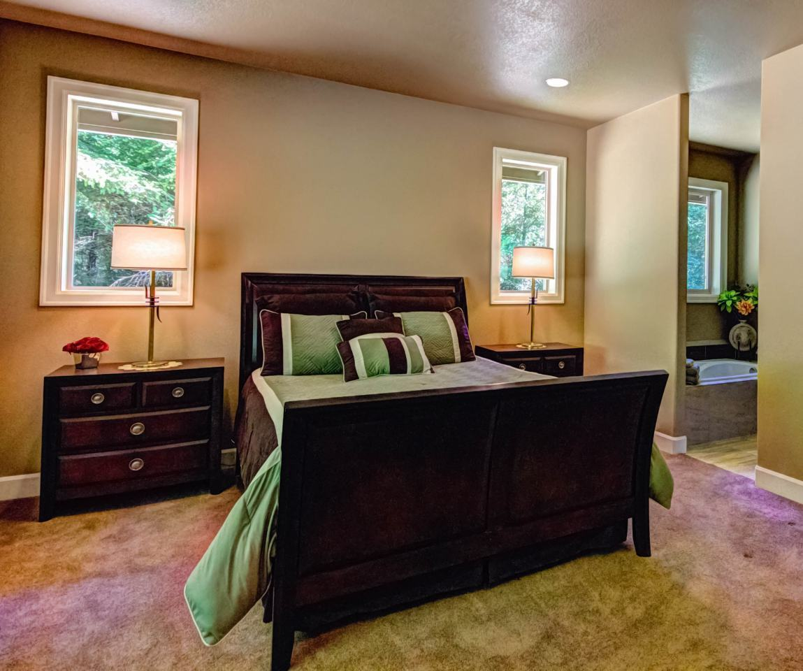 Primary bedroom with beige carpet flooring and a dark wood bed flanked by matching nightstands and drum table lamps.