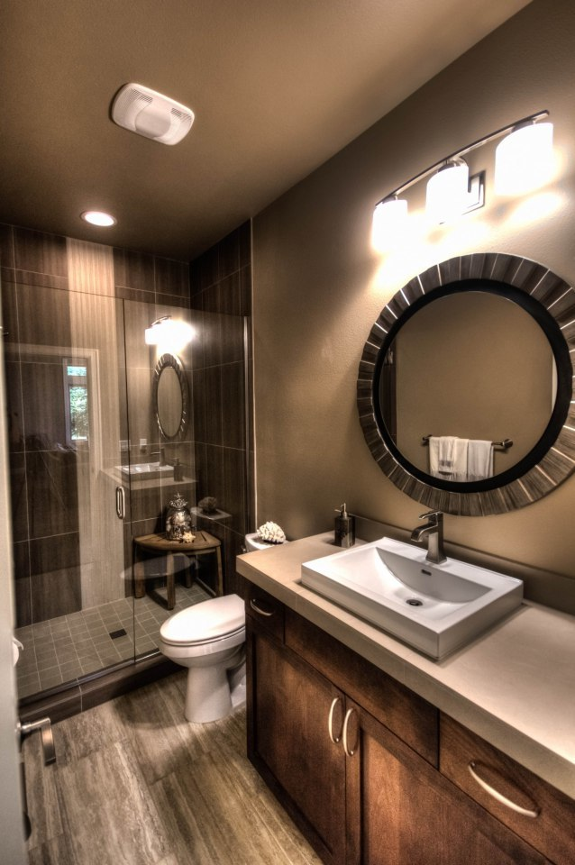 This bathroom offers a walk-in shower, a toilet, and a vessel sink vanity paired with a stylish round mirror.
