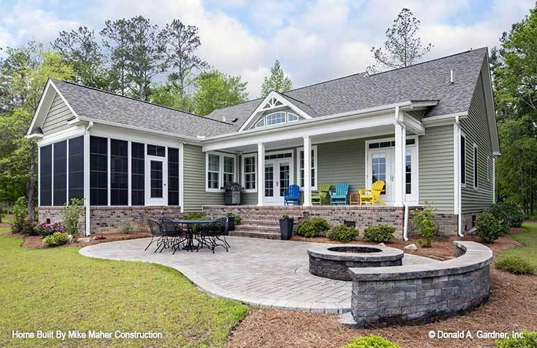 Rear exterior view showing the screened porch and an open patio filled with metal dining set and a fire pit seating.