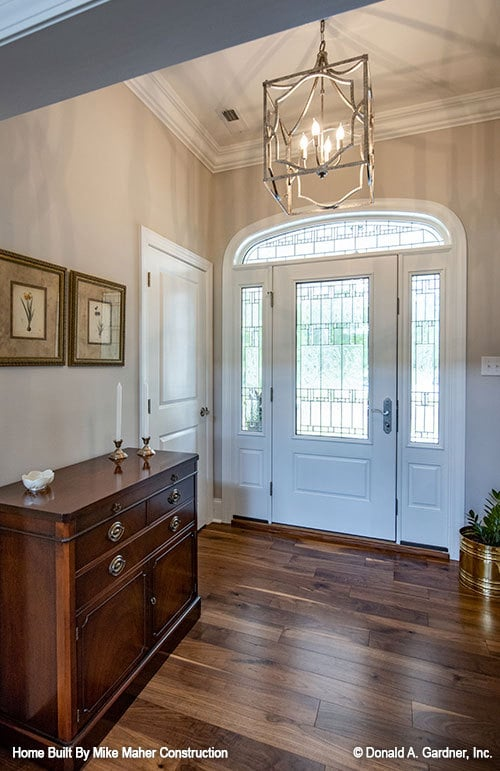 The foyer has a white entry door, ornate chandelier, and a wooden console table adorned with floral artworks.