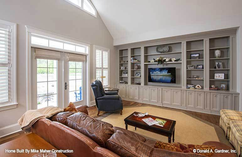 Living room with vaulted ceiling, taupe built-ins, and a french door that opens to the rear porch.