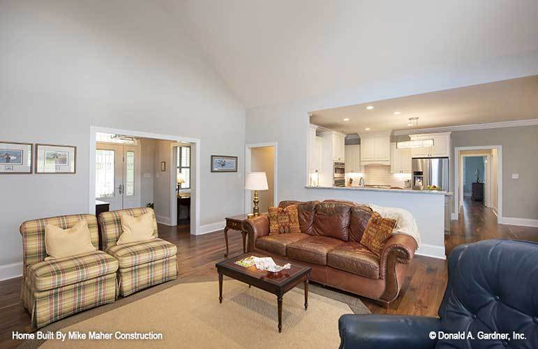 The living room is furnished with a leather sectional, checkered chairs, and a wooden coffee table that sits on an octagonal area rug.