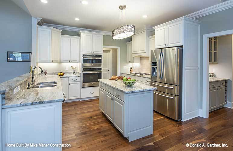 Kitchen with white cabinetry, stainless steel appliances, granite countertops, and a center island illuminated by a glass chandelier.