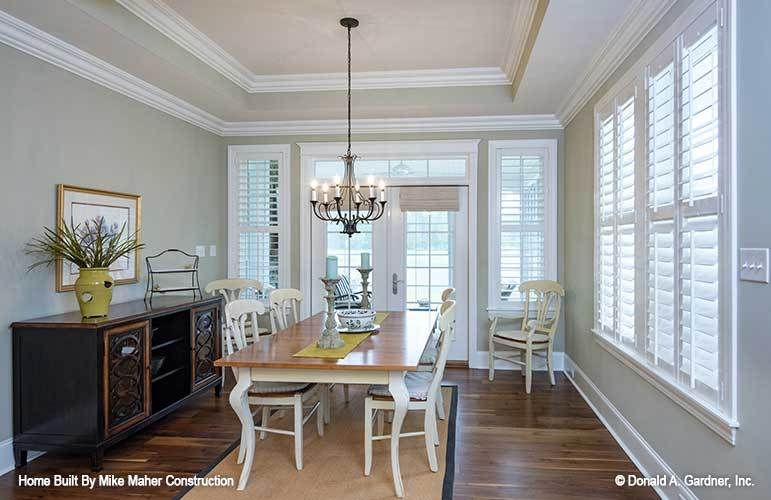 The formal dining room offers a dark wood buffet, white chairs, a rectangular table, and a candle chandelier that hangs from the tray ceiling.