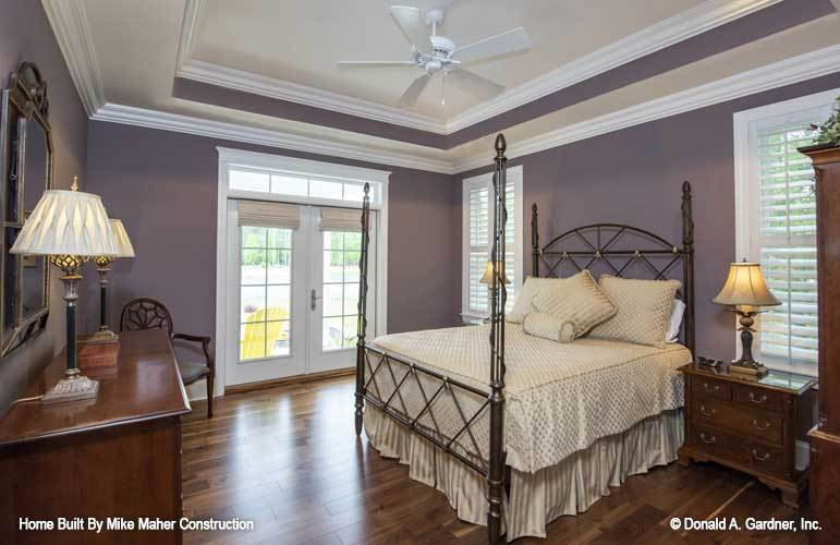 Primary bedroom with a step ceiling, purple walls, a four-poster bed, and wooden cabinets that blend in with the hardwood flooring.