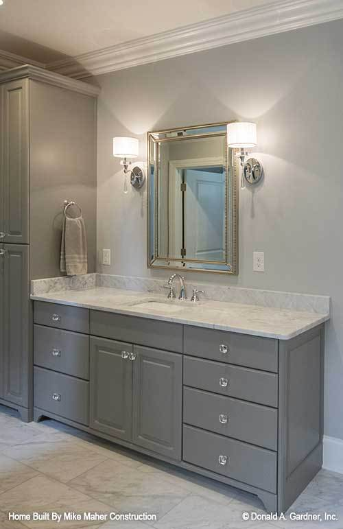 Drum sconces and a chrome framed mirror is fixed above the marble top vanity.