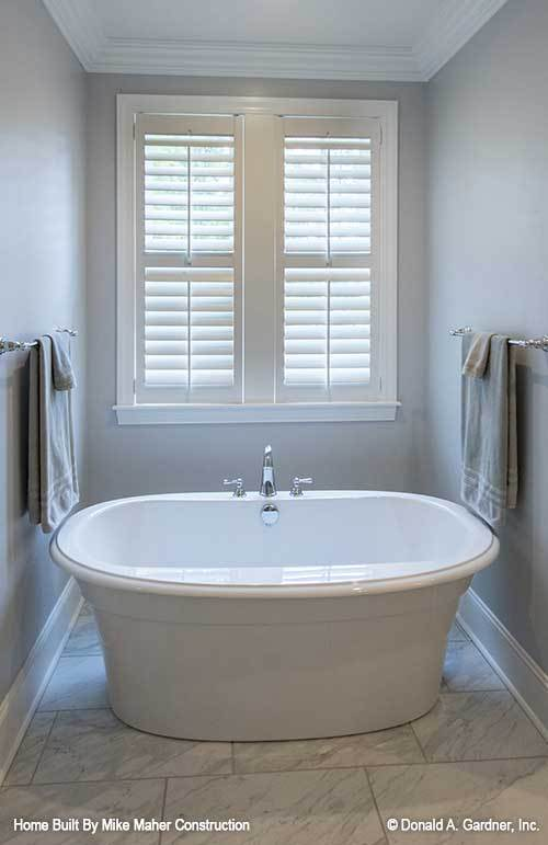 The primary bathroom features a freestanding tub that sits near the white louvered window.