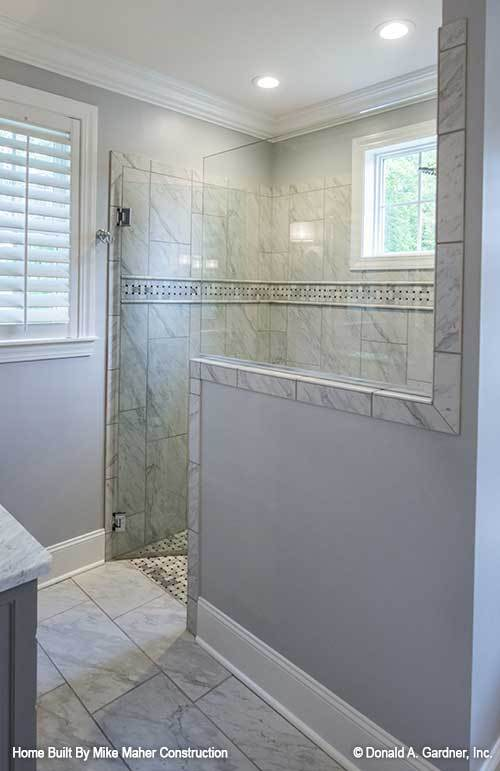 Walk-in shower with marble tiled walls and a hinged glass door.
