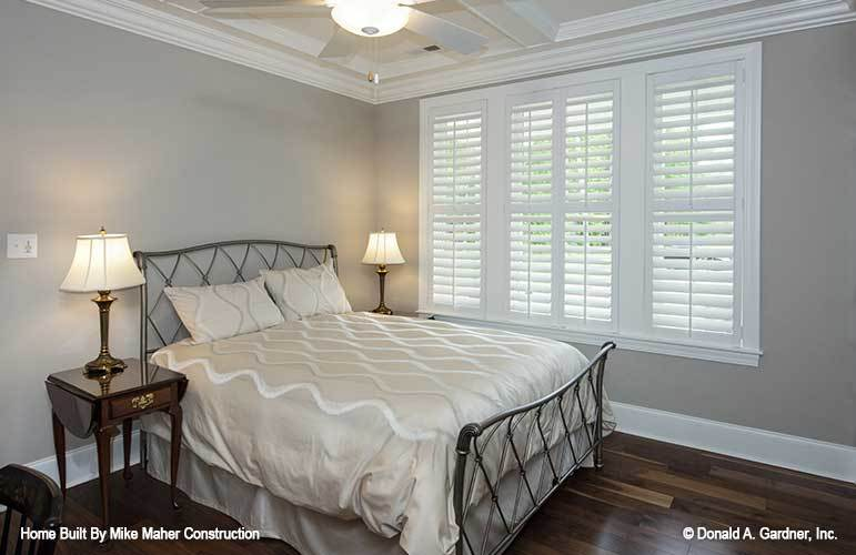 This bedroom has a coffered ceiling and, dark hardwood flooring, and a metal bed flanked with nightstands