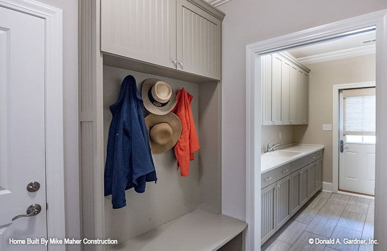 The mudroom leads to the utility room filled with gray modular cabinets.