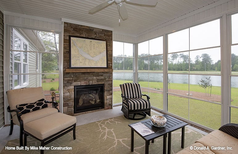 Screened porch with a stone fireplace, cushioned seats, dark wood coffee table, and a printed area rug.